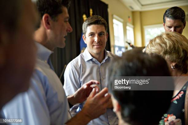 Bryan Steil a Republican US Representative candidate from Wisconsin center listens as US House Speaker Paul Ryan a Republican from Wisconsin left...