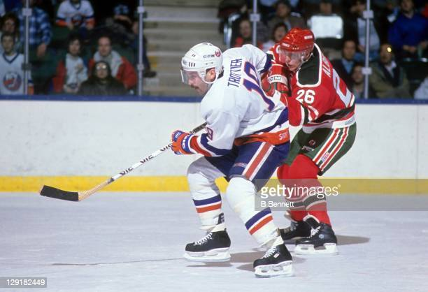 Bryan Trottier of the New York Islanders and Tommy Albelin of the New Jersey Devils go for the puck during their game on December 17 1988 at the...