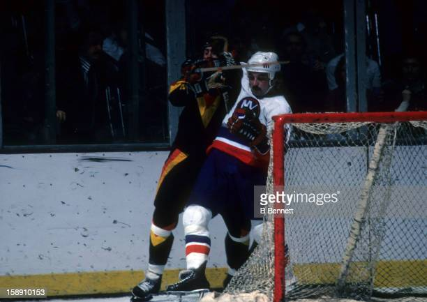 Bryan Trottier of the New York Islanders battles with an unidentified Vancouver Canucks player during their game on January 2 1979 at the Nassau...