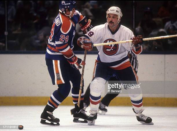 Bryan Trottier of the New York Islanders checks Kevin McClelland of the Edmonton Oilers during the 1984 Stanley Cup Finals in May 1984 at the Nassau...