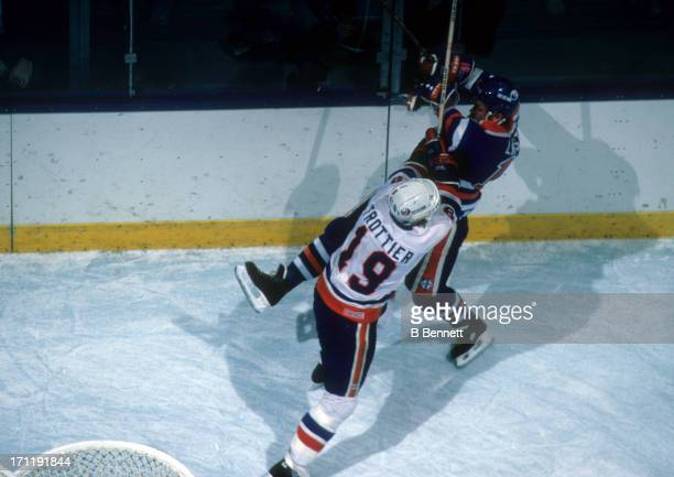 Bryan Trottier of the New York Islanders checks Willy Lindstrom of the Edmonton Oilers during the 1984 Stanley Cup Finals in May 1984 at the Nassau...