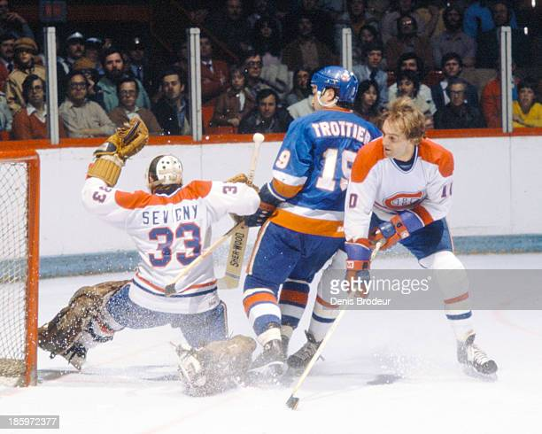 Bryan Trottier of the New York Islanders is sandwiched between goalie Richard Sevigny and Guy LaFleur of the Montreal Canadiens during an attempted...
