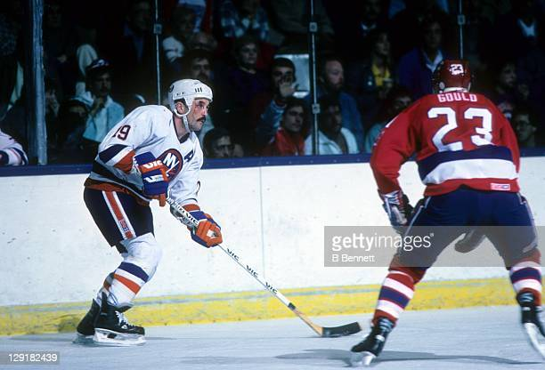 Bryan Trottier of the New York Islanders looks to pass the puck as Bobby Gould of the Washington Capitals charges in during their game on November 4,...