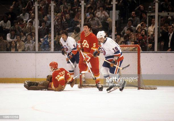Bryan Trottier of the New York Islanders skates on the ice with Brad Marsh of the Atlanta Flames on March 3 1979 at the Nassau Coliseum in Uniondale...