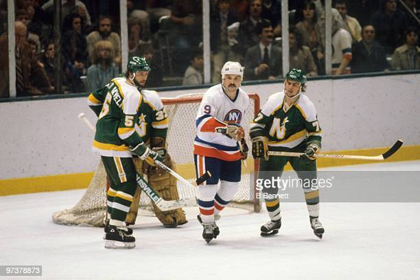 Bryan Trottier of the New York Islanders skates past the low slot area between Brad Maxwell and Neal Broten of the Minnesota North Stars during the...