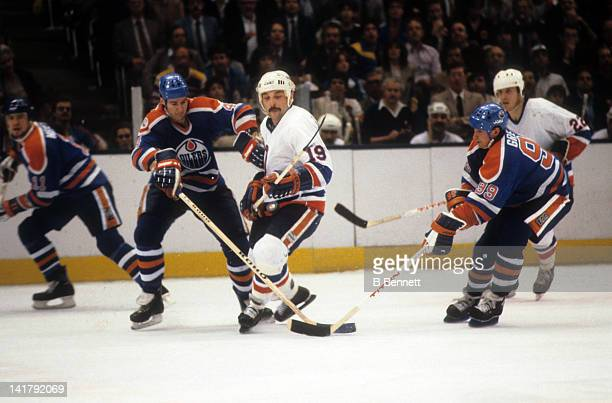 Bryan Trottier of the New York Islanders skates with the puck as Wayne Gretzky and Kevin Lowe of the Edmonton Oilers look to poke check it away...