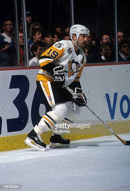 Bryan Trottier of the Pittsburgh Penguins controls the puck behind the net during an NHL game circa 1990 at the Pittsburgh Civic Center in Pittsburgh...
