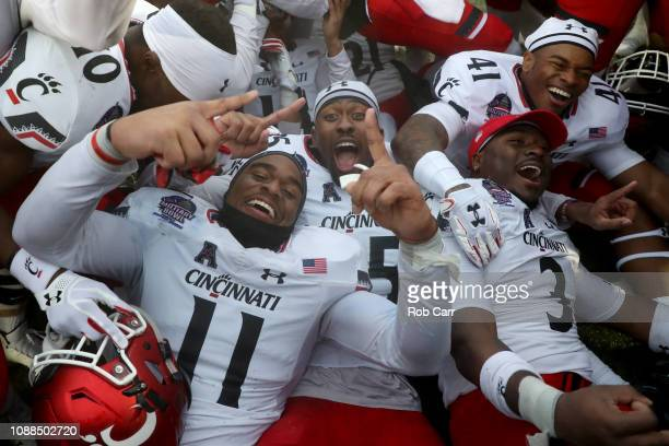 Bryan Wright of the Cincinnati Bearcats celebrates with teammates following their 35-31 win over Virginia Tech Hokies in the Military Bowl at...
