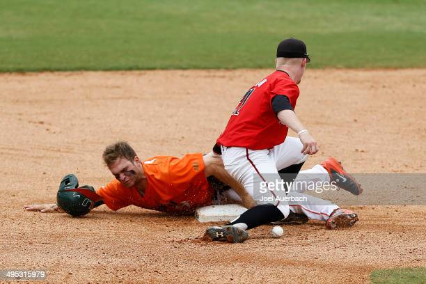 Bryant Burleson of the Texas Tech Red Raiders can not control the ball as Tyler Palmer of the Miami Hurricanes steals second base in the tenth inning...