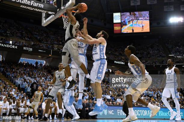 Bryant Crawford of the Wake Forest Demon Deacons goes to the basket against Garrison Brooks and Luke Maye of the North Carolina Tar Heels at Dean...