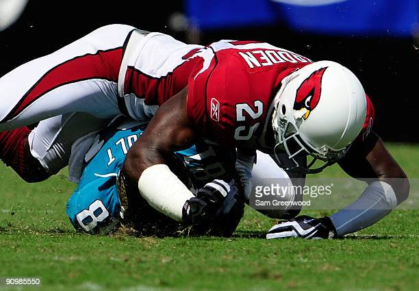 Bryant McFadden of the Arizona Cardinals tackles Tory Holt of the Jacksonville Jaguars during the game at Jacksonville Municipal Stadium on September...