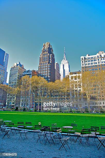 bryant park's folding chairs, grass and trees, with american radiator building (aka american standard building and now bryant park hotel), 1924 by raymond hood and john howells, and empire state building, built 1931 by shreve, lamb and harmon - ブライアント公園 ストックフォトと画像