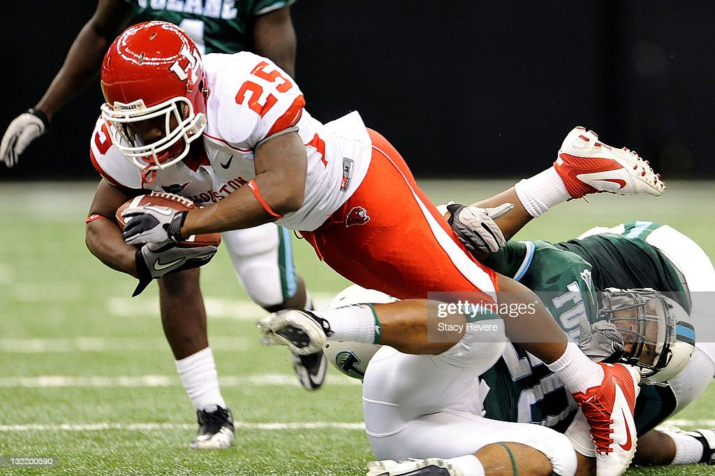 Bryce Beall #25 of the University of Houston Cougars is tripped up by Trent Mackey #20 of the Tulane Green Wave during a game being held at the Mercedes-Benz Superdome on November 10, 2011 in New Orleans, Louisiana.