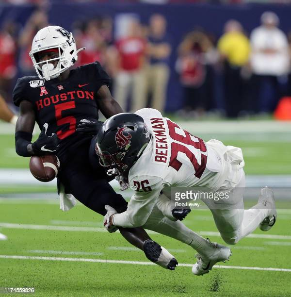 Bryce Beekman of the Washington State Cougars forces Marquez Stevenson of the Houston Cougars to fumble the ball in the fourth quarter during the...