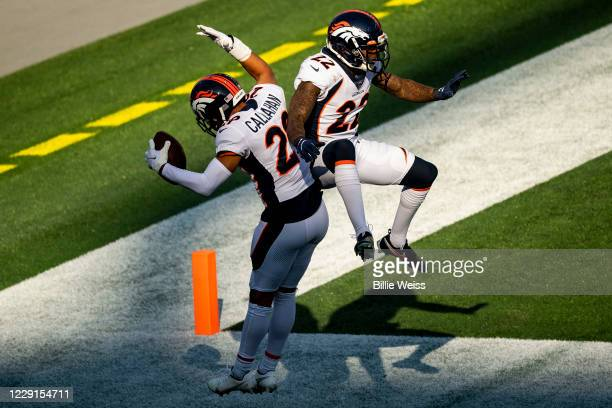 Bryce Callahan of the Denver Broncos reacts with Devontae Harris after an interception during the half of a game against the New England Patriots at...