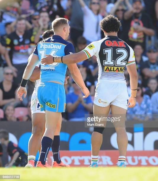 Bryce Cartwright of the Titans gets a pat from Corey HarawiraNaera of the Panthers as he is sinbinned during the round six NRL match between the...