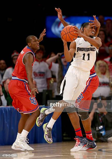 Bryce Cotton of the Providence Friars is pressured by Phil Greene IV and Orlando Sanchez of the St John's Red Storm in the final minutes of the game...