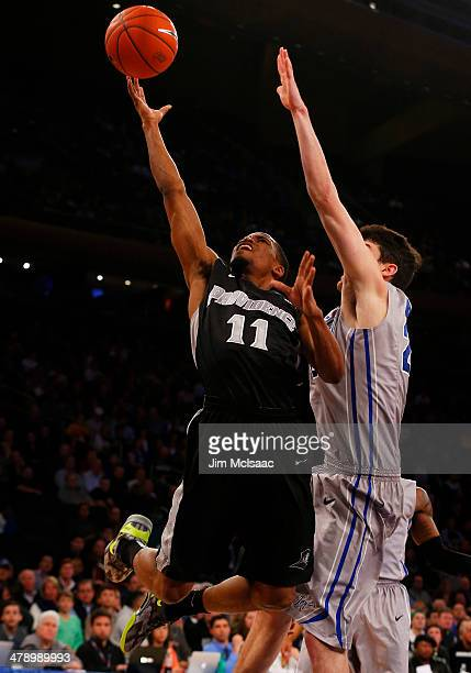 Bryce Cotton of the Providence Friars shoots against John Burns of the Creighton Bluejays in the second half during the Championship game of the 2014...