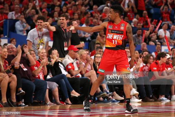 Bryce Cotton of the Wildcats gestures to NBL commentator Corey Williams after making a 3 point shot and being fouled during the round 15 NBL match...