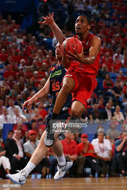Bryce Cotton of the Wildcats lays up against Mitch McCarron of the Taipans during the round 16 NBL match between the Perth Wildcats and the Cairns...