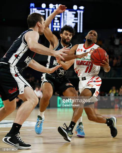Bryce Cotton of the Wildcats runs with the ball under pressure from Sam McDaniel of United and Mitch McCarron of United during the round 16 NBL match...