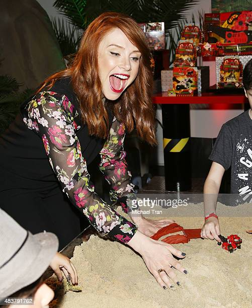 Bryce Dallas Howard plays in the sandbox with 'Dinotrux' toys at the Netflix And DreamWorks' 'Dinotrux' party held at Hollywood Athletic Club on...