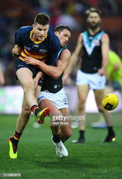 Bryce Gibbs of the Adelaide Crows gets the kick away tackled by Travis Boak captain of Port Adelaide during the round 20 AFL match between the...