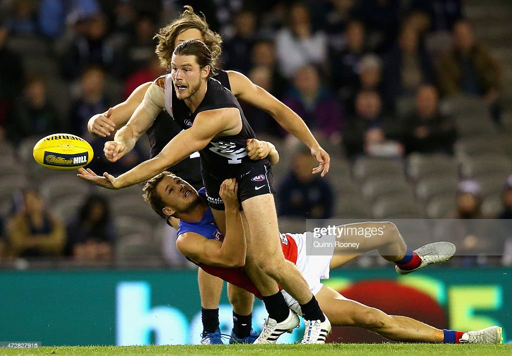 Bryce Gibbs of the Blues handballs whilst being tackled by Jack Redden of the Lions during the round six AFL match between the Carlton Blues and the Brisbane Lions at Etihad Stadium on May 10, 2015 in Melbourne, Australia.
