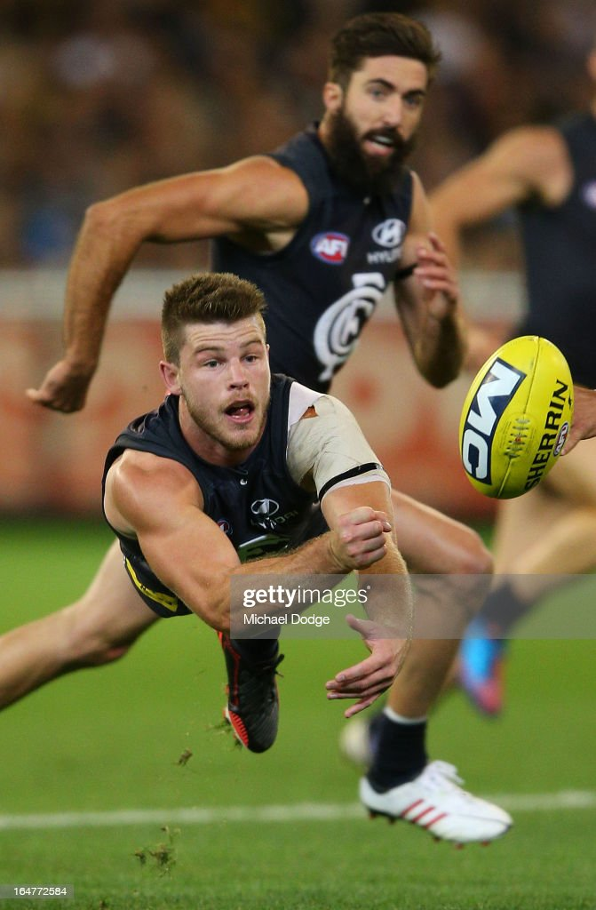 A Bryce Gibbs of the Blues handpasses the ball during the round one AFL match between the Carlton Blues and the Richmond Tigers at Melbourne Cricket Ground on March 28, 2013 in Melbourne, Australia.