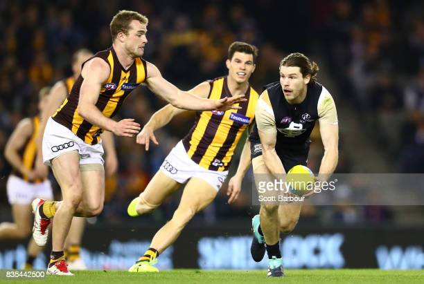 Bryce Gibbs of the Blues is tackled by Tom Mitchell of the Hawks during the round 22 AFL match between the Carlton Blues and the Hawthorn Hawks at...