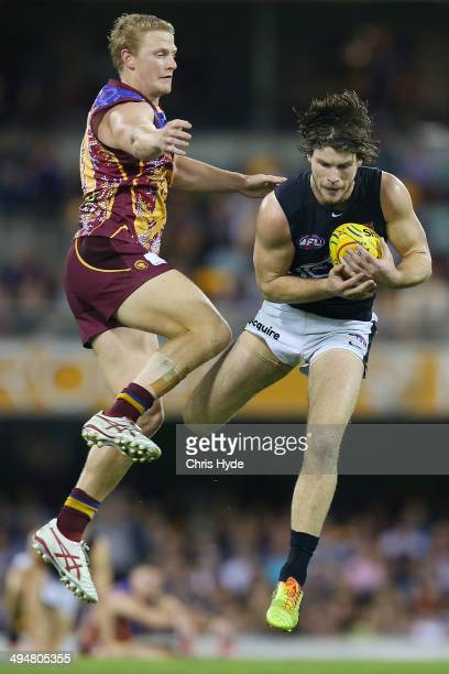 Bryce Gibbs of the Blues takes a mark over Mitch Golby of the Lions during the round 11 AFL match between the Brisbane Lions and the Carlton Blues at...