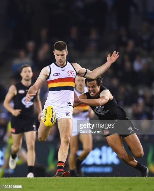 Bryce Gibbs of the Crows kicks whilst being tackled by Jack Silvagni of the Blues during the round 23 AFL match between the Carlton Blues and the...
