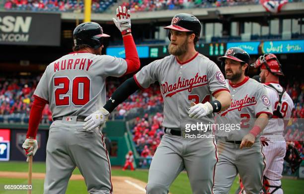 Bryce Harper and Adam Eaton of the Washington Nationals are congratulated by Daniel Murphy after both scored on Harper's two run home run during the...