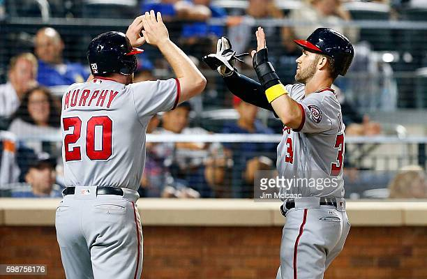 Bryce Harper and Daniel Murphy of the Washington Nationals celebrate after both scored in the ninth inning against the New York Mets at Citi Field on...