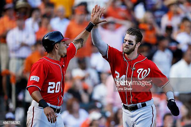 Bryce Harper and Ian Desmond of the Washington Nationals celebrate after they scored in the seventh inning against the San Francisco Giants during...