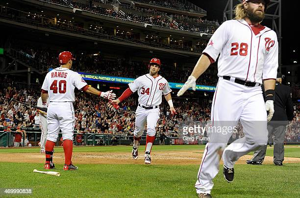 Bryce Harper and Jayson Werth of the Washington Nationals score in the sixth inning against the Philadelphia Phillies at Nationals Park on April 16...