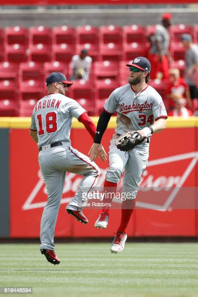 Bryce Harper and Ryan Raburn of the Washington Nationals celebrate after the final out in the ninth inning of a game against the Cincinnati Reds at...