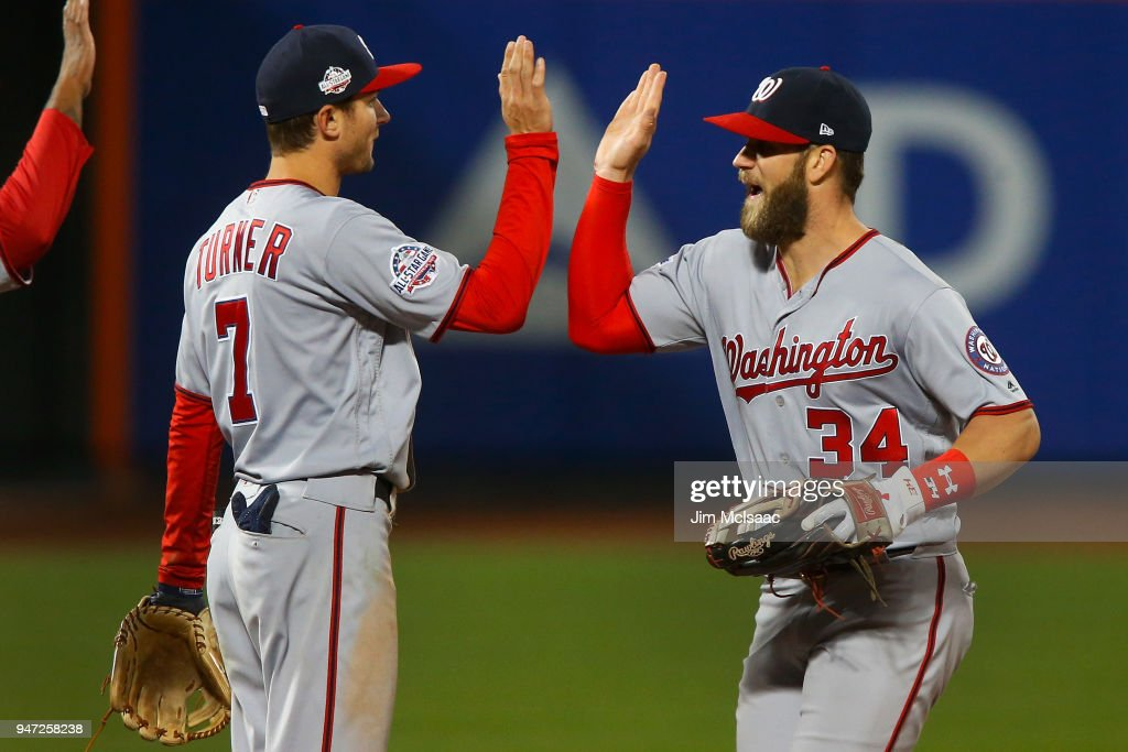 Bryce Harper #34 and Trea Turner #7 of the Washington Nationals celebrate after defeating the New York Mets at Citi Field on April 16, 2018 in the Flushing neighborhood of the Queens borough of New York City.