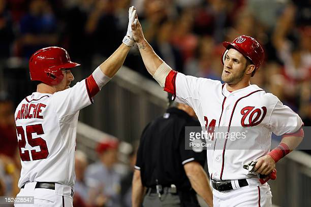 Bryce Harper celebrates scoring with teammate Adam LaRoche of the Washington Nationals during the third inning against the Los Angeles Dodgers at...