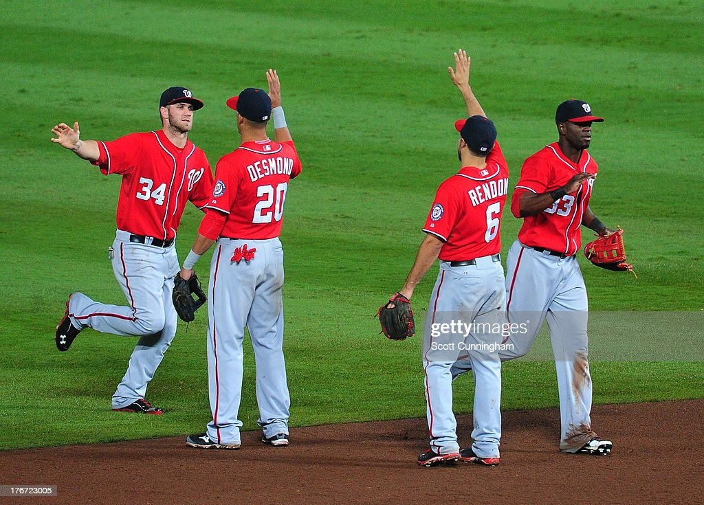Bryce Harper #34, Ian Desmond #20, Anthony Rendon #6, and Roger Bernadina #33 of the Washington Nationals celebrate after the game against the Atlanta Braves at Turner Field on August 17, 2013 in Atlanta, Georgia.