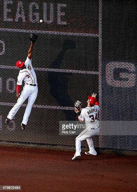 Bryce Harper looks on as center fielder Michael Taylor of the Washington Nationals misses an RBI triple hit by Jay Bruce of the Cincinnati Reds...