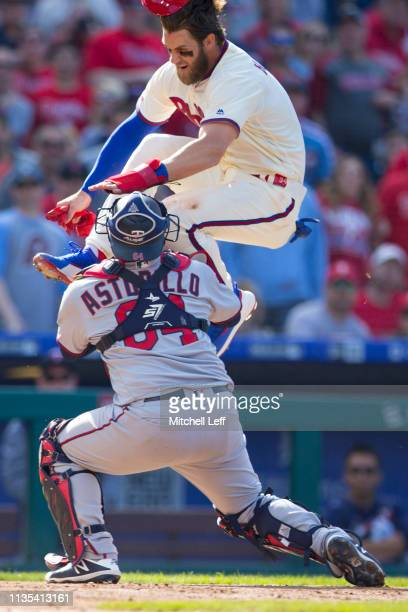 Bryce Harper of the Philadelphia Phillies attempts to score past Willians Astudillo of the Minnesota Twins but is tagged out in the bottom of the...