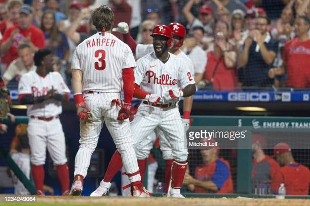 Bryce Harper of the Philadelphia Phillies celebrates with Andrew McCutchen after hitting an inside-the-park home run in the bottom of the fifth...