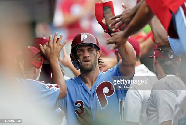 Bryce Harper of the Philadelphia Phillies highfives teammates in the dugout after scoring a run in the seventh inning during a game against the Los...