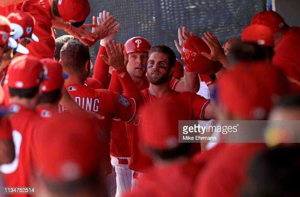 Bryce Harper of the Philadelphia Phillies is congratulated after scoring in the first inning during a game against the Toronto Blue Jays on March 09...