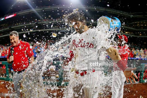 Bryce Harper of the Philadelphia Phillies is doused with water by teammate Jean Segura after hitting a walk-off two run double in the ninth inning to...