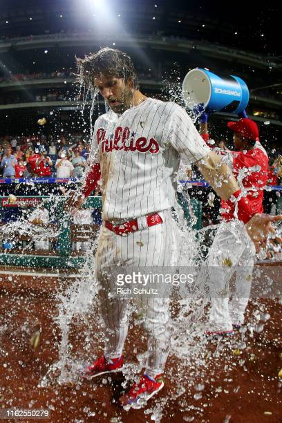 Bryce Harper of the Philadelphia Phillies is doused with water by teammate Jean Segura after hitting a walkoff two run double in the ninth inning to...