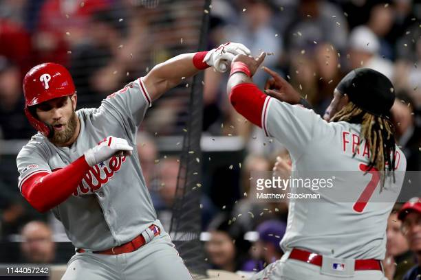 Bryce Harper of the Philadelphia Phillies is showered with seeds by Maikel Franco as he heads into the dugout after hitting a 3 RBI home run in the...