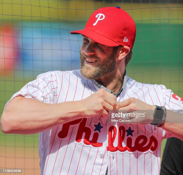 Bryce Harper of the Philadelphia Phillies puts on his new jersey during the press conference introducing Harper as a member of the Philadelphia...