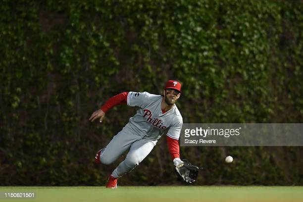 Bryce Harper of the Philadelphia Phillies reaches for a fly ball during the fourth inning against the Chicago Cubs at Wrigley Field on May 20 2019 in...